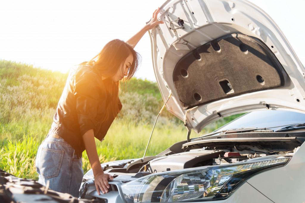 woman checking car engine